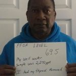Man holding sign: PFOA Levell 69.5